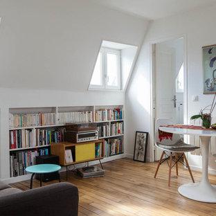 Exemple d'un petit salon avec une bibliothèque ou un coin lecture tendance ouvert avec un mur blanc, un sol en bois brun, aucune cheminée et aucun téléviseur.