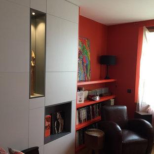 Foto de biblioteca en casa abierta, actual, grande, sin chimenea y televisor, con parades naranjas, suelo de madera clara y suelo amarillo