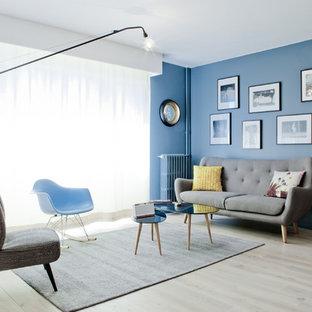 Cette image montre un salon vintage de taille moyenne et fermé avec une salle de réception, un mur bleu, un sol en bois clair, aucune cheminée et aucun téléviseur.