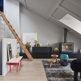 Cette image montre un salon mansardé ou avec mezzanine design de taille moyenne avec un mur gris, un sol en bois clair, aucun téléviseur et un poêle à bois.