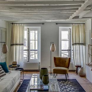 Idées déco pour un petit salon bord de mer fermé avec un mur blanc, un sol en bois brun, aucune cheminée, aucun téléviseur et un sol marron.