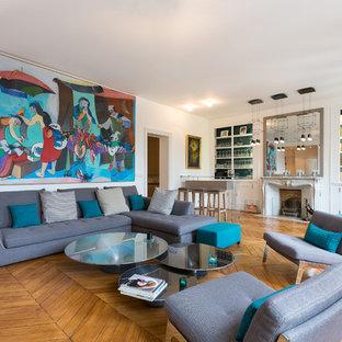 Cette photo montre un salon avec une bibliothèque ou un coin lecture tendance avec un mur blanc, un sol en bois clair et une cheminée standard.