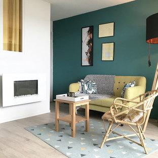他の地域の小さいビーチスタイルのおしゃれなLDK (緑の壁、ラミネートの床、標準型暖炉、金属の暖炉まわり、壁掛け型テレビ、ベージュの床) の写真