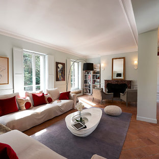Diseño de biblioteca en casa abierta, minimalista, grande, sin televisor, con paredes verdes, suelo de baldosas de terracota, chimenea tradicional y marco de chimenea de piedra