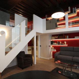 Réalisation d'un grand salon avec une bibliothèque ou un coin lecture design ouvert avec un mur rouge, un sol en bois brun, aucune cheminée et aucun téléviseur.
