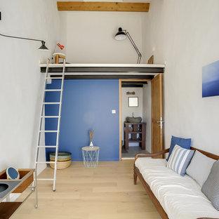 Aménagement d'un salon mansardé ou avec mezzanine scandinave avec un mur blanc, un sol en bois clair et un sol beige.