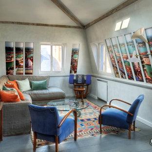 Réalisation d'un salon bohème de taille moyenne avec un sol en bois peint, aucune cheminée, aucun téléviseur et un mur gris.