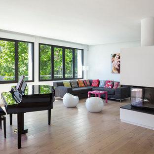 Aménagement d'un grand salon contemporain ouvert avec une salle de musique, un mur blanc, un sol en bois brun, une cheminée double-face, un manteau de cheminée en plâtre et aucun téléviseur.