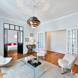Immagine di un soggiorno bohémian di medie dimensioni e chiuso con pavimento in legno massello medio, sala formale, pareti grigie, camino classico e nessuna TV