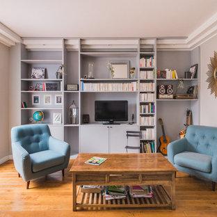 Idée de décoration pour un salon avec une bibliothèque ou un coin lecture tradition fermé avec un mur gris, un sol en bois brun, un téléviseur indépendant et aucune cheminée.