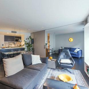 Réalisation d'un grand salon design ouvert avec un mur gris, un sol en bois foncé, aucune cheminée et aucun téléviseur.