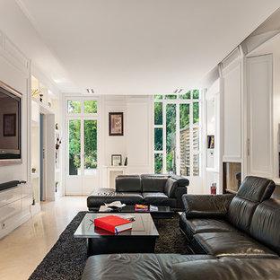 Cette photo montre un salon avec une bibliothèque ou un coin lecture tendance ouvert et de taille moyenne avec un mur blanc, un sol en travertin et un téléviseur encastré.