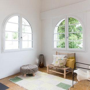 Cette image montre un salon vintage avec un mur blanc, un sol en liège, un poêle à bois et un manteau de cheminée en métal.