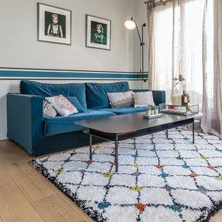 Idée de décoration pour un grand salon nordique avec un mur blanc, un sol en bois clair, aucune cheminée et aucun téléviseur.
