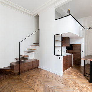 Imagen de salón abierto, contemporáneo, pequeño, sin chimenea, con paredes blancas, suelo de madera en tonos medios, marco de chimenea de yeso, televisor retractable y suelo marrón