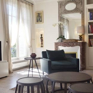 Aménagement d'un grand salon avec une bibliothèque ou un coin lecture contemporain fermé avec un mur blanc, un sol en bois clair, une cheminée standard, un manteau de cheminée en pierre et aucun téléviseur.
