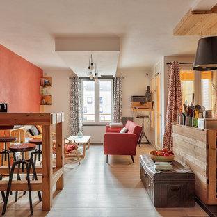 Cette photo montre un salon montagne ouvert avec un mur orange, un sol en bois clair et un sol beige.