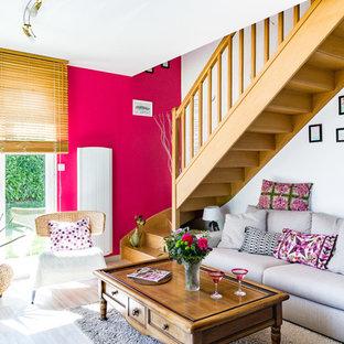 Ejemplo de salón abierto, escandinavo, de tamaño medio, con paredes rosas, suelo de madera clara, estufa de leña, marco de chimenea de metal, televisor independiente y suelo gris