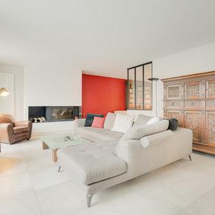 パリの大きいコンテンポラリースタイルのおしゃれなLDK (グレーの壁、セラミックタイルの床、両方向型暖炉、漆喰の暖炉まわり、据え置き型テレビ、ベージュの床) の写真