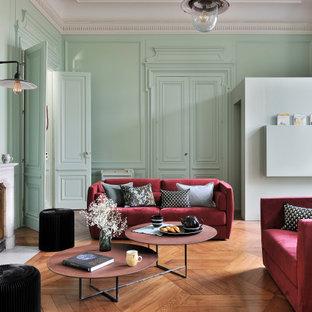 Exemple d'un salon avec une bibliothèque ou un coin lecture tendance de taille moyenne et ouvert avec un mur vert, un sol en bois clair, une cheminée standard, un manteau de cheminée en pierre, un téléviseur dissimulé et un sol beige.