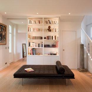 Exemple d'un salon avec une bibliothèque ou un coin lecture chic de taille moyenne et ouvert avec un mur blanc, un sol en bois brun, aucune cheminée et aucun téléviseur.