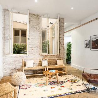 Aménagement d'un salon scandinave avec un mur blanc, un sol en bois clair et un sol beige.