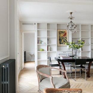 Immagine di un soggiorno classico di medie dimensioni e aperto con libreria, pareti bianche, parquet chiaro, nessun camino e nessuna TV