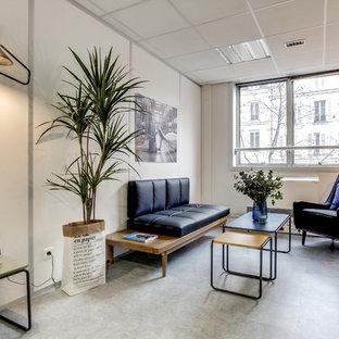 Cette photo montre un salon scandinave fermé et de taille moyenne avec un mur blanc, béton au sol et un sol gris.