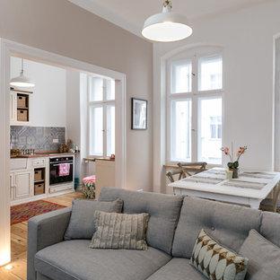 Mittelgroßes, Repräsentatives, Fernseherloses, Offenes Modernes Wohnzimmer ohne Kamin mit weißer Wandfarbe, braunem Holzboden und braunem Boden in Berlin