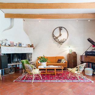 Aménagement d'un salon éclectique avec une salle de réception, un mur blanc, un sol en carreau de terre cuite, une cheminée d'angle, aucun téléviseur et un sol rouge.