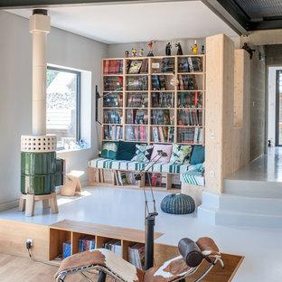 Immagine di un soggiorno industriale aperto con pareti bianche, stufa a legna e pavimento bianco