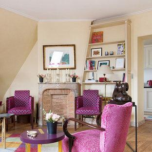 Inspiration pour un salon bohème de taille moyenne et fermé avec une salle de réception, un mur beige, un sol en bois clair, une cheminée standard, un manteau de cheminée en pierre et aucun téléviseur.