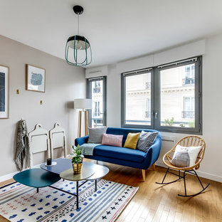 Inspiration pour un petit salon nordique ouvert avec un mur blanc et un sol en bois clair.