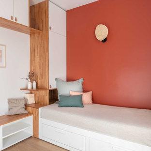 Kleines, Abgetrenntes Modernes Wohnzimmer ohne Kamin mit roter Wandfarbe, hellem Holzboden und Wand-TV in Paris