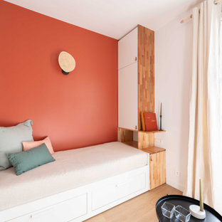 Idéer för ett litet modernt separat vardagsrum, med ett bibliotek, röda väggar, ljust trägolv och en väggmonterad TV