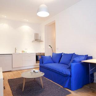 Aménagement d'un petit salon contemporain ouvert avec un mur blanc, un sol en bois clair, aucune cheminée, aucun téléviseur et un sol marron.