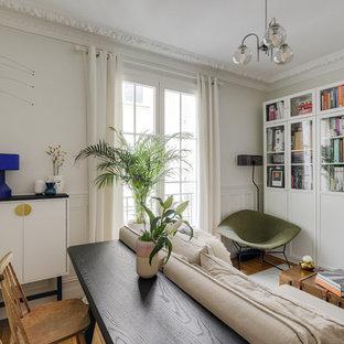 Réalisation d'un salon avec une bibliothèque ou un coin lecture tradition fermé avec un mur blanc, un sol en bois brun et un sol marron.