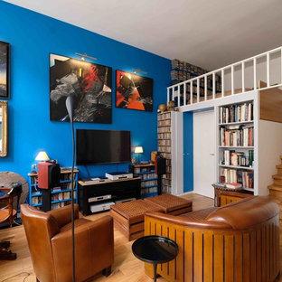 Exemple d'un petit salon avec une bibliothèque ou un coin lecture éclectique ouvert avec un mur bleu, un sol en bois clair et un téléviseur fixé au mur.