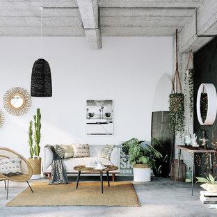 リヨンのトロピカルスタイルのおしゃれなリビング (白い壁、コンクリートの床、グレーの床) の写真