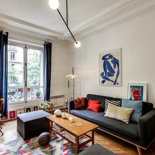 Inspiration pour un salon avec une bibliothèque ou un coin lecture traditionnel de taille moyenne et fermé avec un mur blanc, un sol en bois brun, aucune cheminée et aucun téléviseur.