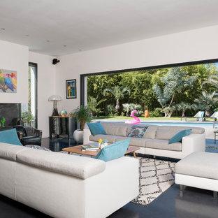 Aménagement d'un salon contemporain avec un mur blanc, béton au sol, une cheminée ribbon et un sol noir.