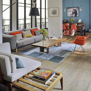Idées déco pour un salon éclectique avec un mur blanc et un sol en bois clair.