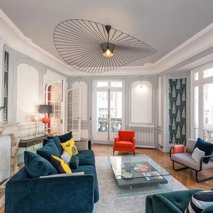 Réalisation d'un grand salon design fermé et haussmannien avec une salle de réception, un mur multicolore, un sol en bois brun et une cheminée standard.