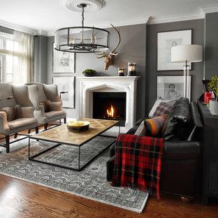 Cette image montre un salon traditionnel ouvert et de taille moyenne avec une salle de réception, un mur gris, un sol en bois brun, une cheminée standard et aucun téléviseur.