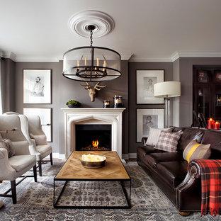 Cette image montre un salon beige et marron bohème de taille moyenne et ouvert avec un mur gris, une cheminée standard, un manteau de cheminée en pierre, aucun téléviseur et une salle de réception.