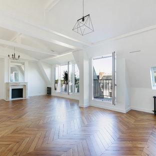 Réalisation d'un très grand salon tradition avec un mur blanc, un sol en bois brun, une cheminée standard, un manteau de cheminée en pierre et aucun téléviseur.