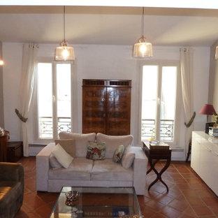 Mediterranes Wohnzimmer mit weißer Wandfarbe, Terrakottaboden und orangem Boden in Sonstige