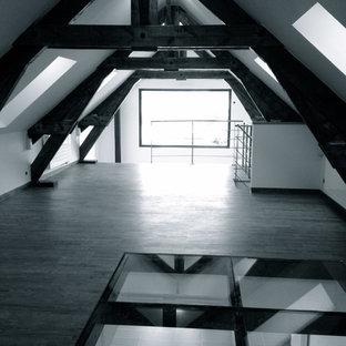 Foto de biblioteca en casa tipo loft, actual, grande, con paredes blancas, suelo de madera clara, estufa de leña y suelo marrón