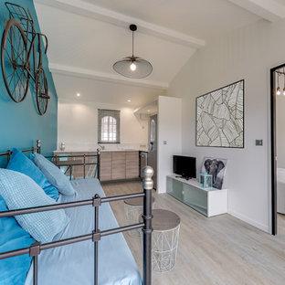 Cette photo montre un salon tendance ouvert avec un mur blanc, un sol en bois clair, un téléviseur indépendant et un sol beige.