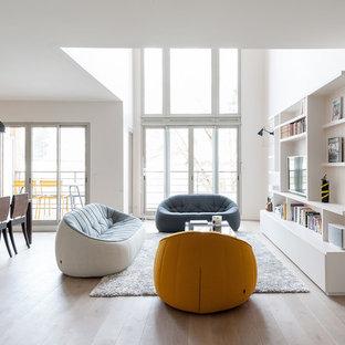 Cette image montre un salon nordique de taille moyenne et ouvert avec une salle de réception, un mur blanc, un sol en bois clair, aucune cheminée et un téléviseur fixé au mur.